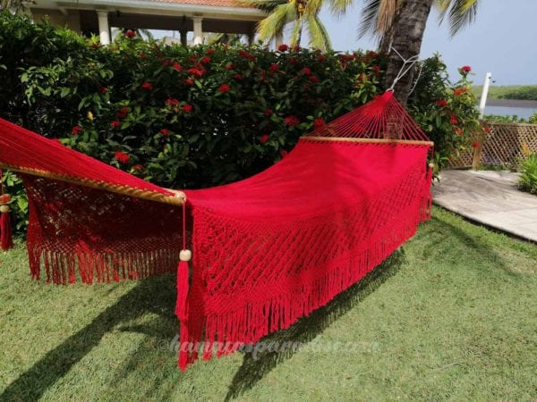 large red hammock hung between 2 coconut tree